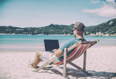 Young hipster man with laptop on tropical beach. Travel, vacatio. N, internet, freelance job concept Stock Image