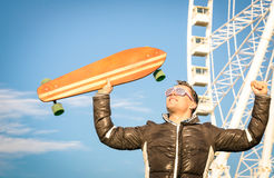 Young hipster man with longboard skate board at luna park Stock Images