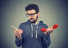 Confused man with old and new phones. Young hipster man looking puzzled about old fashioned and contemporary gadgets stock photos