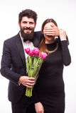 Young hipster man make surprise for his girlfriend and give her a tulips bucket Royalty Free Stock Images