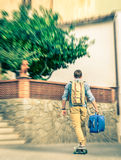Young hipster man moving with his longboard and luggage Royalty Free Stock Photos