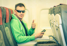 Young hipster man passenger with thumbs up in airplane. Young hipster man passenger satisfied with thumbs up after boarding - Concept of low coast flight and Royalty Free Stock Images