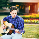 Young hipster man playing guitar in a park Stock Photos