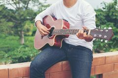 Young hipster man playing guitar to relaxing on his holiday, enjoy with natural and fresh air. royalty free stock photo