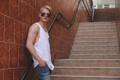 Young hipster man posing standing on the stairs. Blond fit tenager wearing sunglasses, jeans and white t-shirt standing on city stairs. Usual urban days. Male Stock Photo