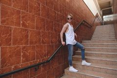 Young hipster man posing standing on the stairs. Blond fit tenager wearing sunglasses, jeans and white t-shirt standing on city stairs. Usual urban days. Male Stock Photography