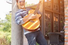 Young hipster man practiced guitar in the park,happy and enjoy playing guitar. royalty free stock photography