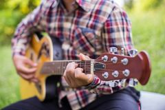 Close up of young hipster man practiced guitar in the park,happy and enjoy playing guitarset stock photography