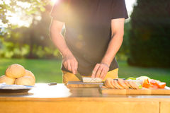 Young hipster man preparing food for garden grill party, summer barbecue Stock Photo