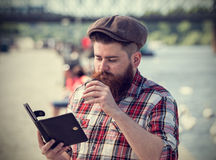Young hipster man reading electronic book Royalty Free Stock Photo
