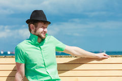 Young hipster man sitting on bench near the sea outdoor Royalty Free Stock Photography