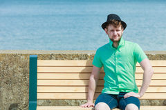 Young hipster man sitting on bench near the sea outdoor Stock Photo