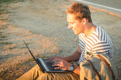 Young hipster man sitting outdoors checking mails on laptop Stock Image