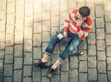 Young hipster man sitting and using cellphone Stock Photos