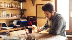 Young hipster man sketching in his studio. Young hipster man sketching on a notebook in his studio on a rustic wooden table Royalty Free Stock Photo