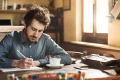 Young hipster man sketching in his studio. Young hipster man sketching on a notebook in his studio on a rustic wooden table Royalty Free Stock Images