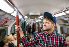 Young hipster man standing in a crowded subway train Royalty Free Stock Image