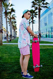 Young hipster man standing on the grass holding his longboard Stock Image