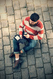 Young hipster man using electronic book Royalty Free Stock Images