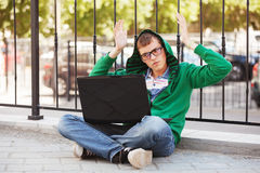 Young hipster man using laptop in city street. Young hipster man in a hoodie using laptop in city street Royalty Free Stock Photography