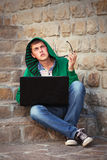 Young hipster man using laptop on the steps. Young hipster man in a hoodie using laptop on the steps Royalty Free Stock Photo