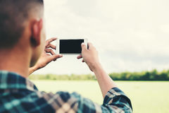 Young hipster man using smartphone taking the landscape photogra Royalty Free Stock Images