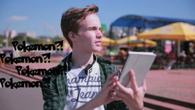 Young hipster man using tablet in the city playing pokemon go. stock video