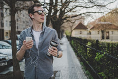 Young hipster man walking on the street and listening music on his smartphone.  Royalty Free Stock Photo