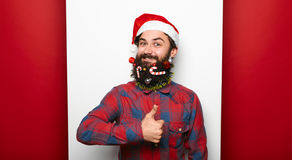 Young hipster man wearing christmas hat with thumb up Stock Photo