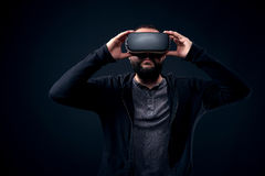 Young hipster man wearing virtual reality goggles. Black background studio VR concept. Young hipster bearded man wearing virtual reality goggles. Black royalty free stock photo