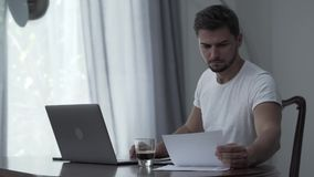 Young hipster manager or freelancer focused on working with laptop and making difficult task sitting on his kitchen. Serious hipster manager or freelancer stock footage