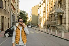 On the Phone. Young hipster with orange jacket, sunglasses, backpack and his smart phone in the city street Stock Photos