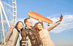 Young hipster people trio taking selfie at luna park ferris whee Royalty Free Stock Images
