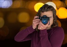 Young hipster photographer taking a photo in the city at nights ( blurred lights). Digital composite of young hipster photographer taking a photo in the city at Stock Images