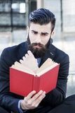 Young hipster reading a book sitting outdoors Stock Photos