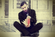 Young hipster reading a book sitting outdoors Royalty Free Stock Images