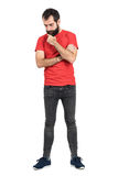 Young hipster in red t-shirt stroking beard white thinking and looking down. Stock Photography
