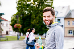 Young hipster runner in town with water bottle, drinking Royalty Free Stock Image