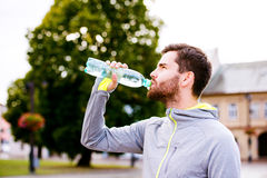 Young hipster runner in town with water bottle, drinking Royalty Free Stock Photos