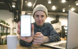 A young hipster shows a phone screen to the camera. A look at the camera. A student works for a laptop in a cozy cafe. A young hipster shows a phone screen to Stock Photo