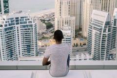 Young Hipster Siting on the top on the rooftop in Dubai Marina - Tomasz Ganclerz Dubai Marina 2017 stock image