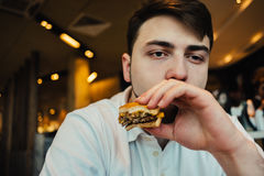 Young hipster sitting in a cafe and eat fast food. delicious burger. Young hipster with a beard sitting in the cafe and eat fast food. delicious burger Royalty Free Stock Photos
