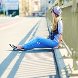Young hipster sitting on city street Stock Photo