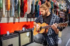 Young hipster sitting and playing on acoustic guitar. He looks down. Guy is concentrated. Many electronic guitars and. Sound columns are behind him royalty free stock images