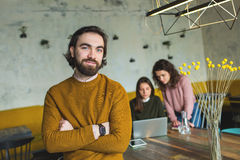 Young hipster with smart watch over two females in cafe. Young hipster with smart watch over two females in trendy cafe Stock Photos