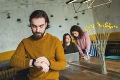 Young hipster with smart watch over two females in cafe stock images