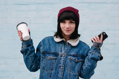 Young hipster smiling girl holding phone and coffee. Hipster young smiling girl in a blue denim jacket, holding phone and coffee on light blue background Royalty Free Stock Images