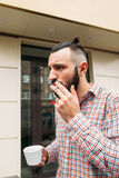 Young hipster smoking with cup of coffee outdoor. Stylish man relaxing with cigarette, free space. Bad addiction, rest, business, smoko concept Stock Photo