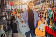 Young hipster stand and hold both electric and acoustic guitars. He looks at yellow one. Guy can`t choose between two. Instruments stock images