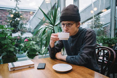 Young hipster student drinks tea in a cafe. lying on the table and phone book, and outside greenhouse with plants. Young hipster student in shirt drinking tea Royalty Free Stock Photos